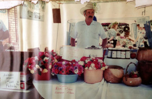 Doug Welburn selling his produce at a farmer's market in 1996 (including, flowers he grew and jam made from his home-grown blackberries).